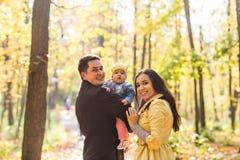 Влюбленность, родительство, семья, сезон и концепция людей - усмехаясь пары с младенцем в осени паркуют стоковое фото