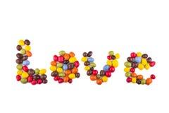 Влюбленность слова написана с поливой покрашенной конфетой Стоковые Фото