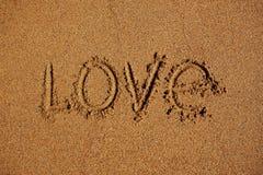 Влюбленность слова написанная на песке Стоковое Изображение RF