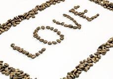 Влюбленность слова написанная от стороны с кофейными зернами и рамка сделанная из кофе Стоковое фото RF