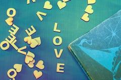 Влюбленность слова написанная с деревянными письмами на голубой предпосылке книга старая Стоковые Изображения