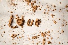 Влюбленность слова от какао, белой предпосылки Стоковое фото RF