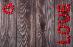 Влюбленность слова от конфеты на деревянной предпосылке связанный вектор Валентайн иллюстрации s 2 сердец дня Стоковая Фотография