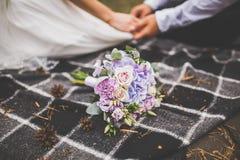 Влюбленныйся жених и невеста сидит на шотландке шотландки держа руки Букет свадьбы рядом Стоковые Фотографии RF