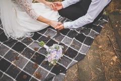 Влюбленныйся жених и невеста сидит на шотландке шотландки держа руки Букет свадьбы рядом Стоковая Фотография RF