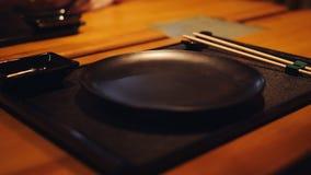 В японском ресторане, таблица и различный традиционный столовый прибо сток-видео