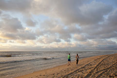 Гаага, Нидерланды, 10-ое августа 2012: jogs пар на пляже Стоковая Фотография RF