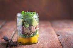 Гаваиский салат Poke с тунцом, авокадоом и овощами в опарнике на деревенской предпосылке стоковое фото rf