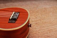 Гавайская гитара Брайна положенная на старую таблицу древесины Брайна Стоковые Изображения