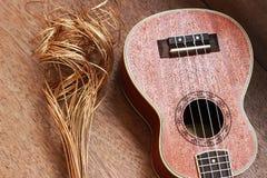 Гавайская гитара Брайна положенная на старую таблицу древесины Брайна Стоковая Фотография
