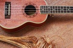 Гавайская гитара Брайна положенная на старую таблицу древесины Брайна Стоковая Фотография RF
