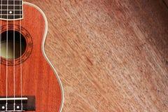 Гавайская гитара Брайна положенная на старую таблицу древесины Брайна Стоковое Изображение