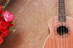 Гавайская гитара Брайна положенная на старую таблицу древесины Брайна Стоковые Изображения RF