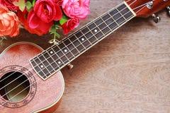 Гавайская гитара Брайна положенная на старую таблицу древесины Брайна Стоковые Фотографии RF
