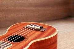 Гавайская гитара Брайна положенная на старую таблицу древесины Брайна Стоковое Фото