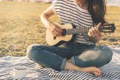 Гавайская гитара женщины на пляже стоковое фото rf