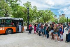 ГАВАНА, КУБА - 22-ОЕ ОКТЯБРЯ 2017: Городской пейзаж Гаваны при местные люди ждать в линии автобусной остановки стоковое изображение