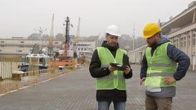Гаван работники в шлемах смотрят документы Морской порт