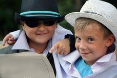 газета читая 2 шлемов мальчиков стоковая фотография