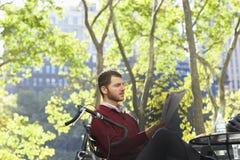 Газета чтения бизнесмена в парке Стоковое Изображение RF