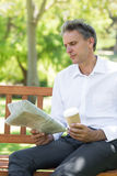 Газета чтения бизнесмена в парке Стоковое фото RF