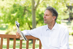 Газета чтения бизнесмена в парке Стоковые Фотографии RF