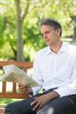 Газета чтения бизнесмена в парке Стоковое Изображение