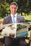 Газета чтения бизнесмена в парке Стоковые Изображения RF