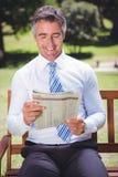 Газета чтения бизнесмена в парке Стоковая Фотография RF