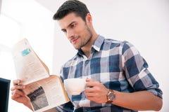 Газета чтения бизнесмена и выпивая кофе в офисе Стоковые Фото