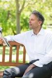 Газета чтения бизнесмена на парке Стоковое Изображение