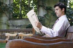 Газета чтения бизнесмена на скамейке в парке Стоковые Фотографии RF