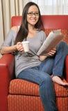 Газета чтения довольно biracial женщины ослабляя стоковое изображение rf