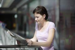 Газета чтения женщины в торговом центре Стоковые Изображения RF