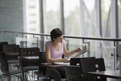 Газета чтения женщины на кафе Стоковая Фотография RF