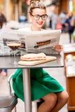 Газета чтения женщины на кафе outdoors Стоковая Фотография