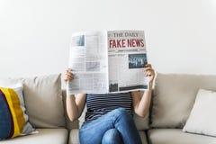 Газета чтения женщины сидя на кресле Стоковые Изображения
