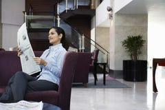 Газета чтения коммерсантки в лобби гостиницы Стоковая Фотография RF