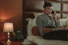 Газета чтения коммерсантки и говорить на сотовом телефоне в горячем стоковое фото