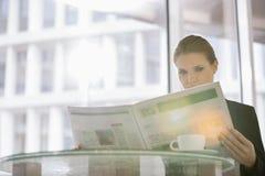 Газета чтения коммерсантки на кафе офиса Стоковые Фото
