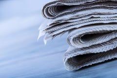 Газеты сложенные и штабелированные на таблице Стоковое Изображение