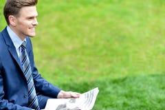 Газеты чтения бизнесмена в парке Стоковое Фото