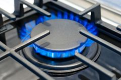 Газовая горелка горит с голубым пламенем на плите под защитным грилем стоковая фотография