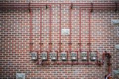 Газовые счетчики и труба на кирпичной стене стоковые фотографии rf