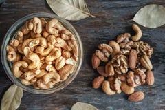 Гайки, грецкие орехи и миндалины анакардии с вискиом на деревянном backgrou Стоковая Фотография