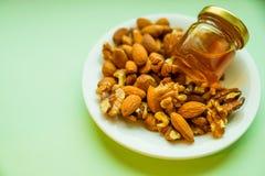 Гайки и мед в малом опарнике, баке на плите, на зеленой предпосылке Обед в офисе Вытрезвитель, есть вегетарианца Стоковая Фотография