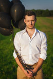 Гай в белой рубашке при черные воздушные шары стоя в поле Стоковые Изображения RF