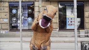 Гай в проказнике костюма rex t идя на crosswalk улицы города акции видеоматериалы