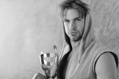 Гай в сером безрукавном hoodie держит золотой приз стоковые фотографии rf