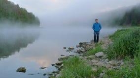 Гай в синем пиджаке наслаждается утром идя вдоль берега озера видеоматериал
